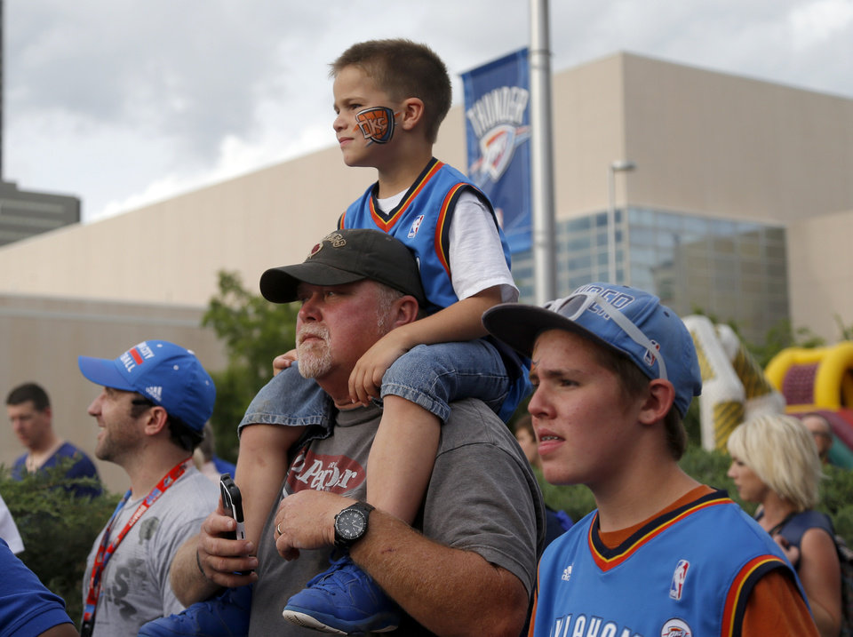 Photo - Jimmy Duggins, holds his 6-year-old son Benjamin on his shoulders beside his other son Blake, 12, outside the arena before Game 3 of the Western Conference Finals in the NBA playoffs between the Oklahoma City Thunder and the San Antonio Spurs at Chesapeake Energy Arena in Oklahoma City, Sunday, May 25, 2014. Photo by Bryan Terry, The Oklahoman