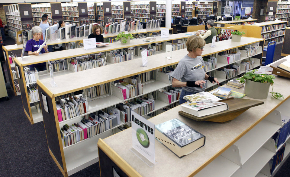 Library aides shelve reserved books as a part of the new system at the Edmond branch of the Metropolitan Library System.