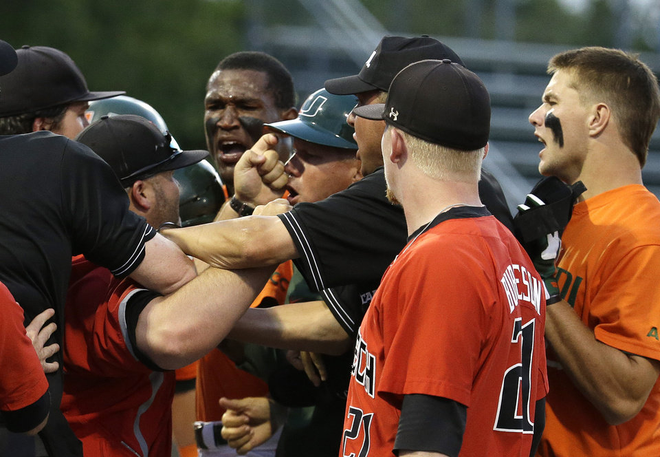 Photo - Miami assistant coach Gino DiMare, fourth from right, argues with a Texas Tech coach, second from left, as they are restrained by umpires after David Thompson, right, was out at first in the third inning during an NCAA college baseball regional tournament in Coral Gables, Fla., Sunday, June 1, 2014. (AP Photo/Lynne Sladky)