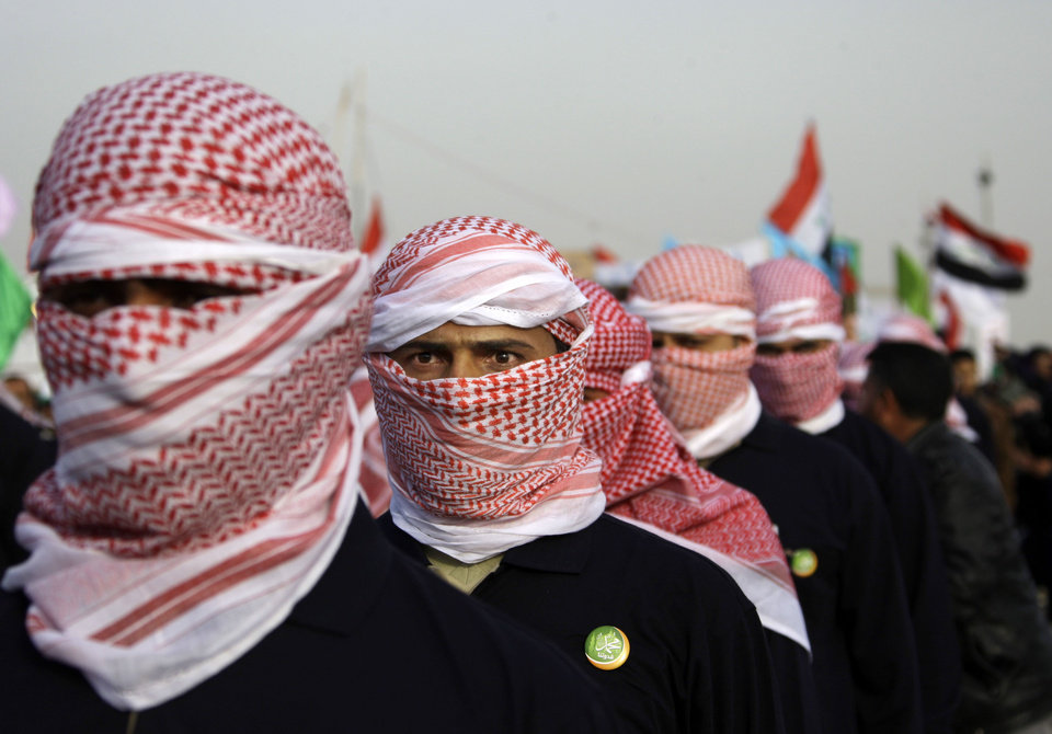 In this Thursday, Jan. 24, 2013 photo, masked men parade during a protest against Iraq's Shiite-led government in Ramadi, 70 miles (115 kilometers) west of Baghdad, Iraq. Iraqi insurgents are trying to capitalize on the rage of anti-government protesters and the instability caused by rising civil unrest, complicating the government's efforts to stamp out a resurgent al-Qaida and other extremists. (AP Photo/ Khalid Mohammed)