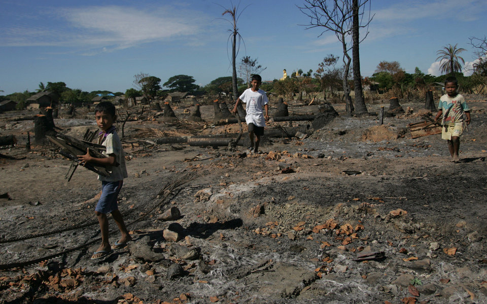 Photo - In this photo taken on Nov. 7, 2012, children carry half-burned wood, debris of burnet down buildings following recent violence, in Pauk Taw, Rakhine state, western Myanmar. The Oct. 24 exodus was part of a wave of violence that has shaken western Myanmar twice in the last six months. But what began with a series of skirmishes that pitted ethnic Rakhine Buddhists against Rohingya, a Muslim minority, appears to have evolved into something far more disturbing: a region-wide effort by Buddhists to drive Muslims out with such ferocious shows of hatred that they could never return. (AP Photo/Khin Maung Win)