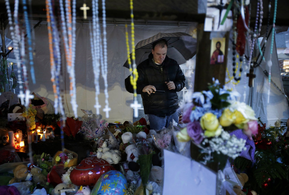 Photo - Ben Toby of Sandy Hook visits a memorial to the Newtown shooting victims during a heavy rain in the Sandy Hook village of Newtown, Conn., Friday, Dec. 21, 2012.  The shooter, Adam Lanza, walked into Sandy Hook Elementary School in Newtown, Dec. 14, and opened fire, killing 26 people, including 20 children, before killing himself.  (AP Photo/Seth Wenig)
