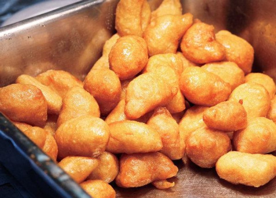 Photo - Loukoumades, a Greek donut-like pastry, fresh out of the hot oil, are kept warm under a heat lamp until they are served to  waiting customers  on Friday, Sep. 9, 2011, during the 27th annual Greek Festival at St. George Greek Orthodox Church in far northwest Oklahoma City.  Gianos said Greek coffee is not percolated but each cup of the  beverage is cooked fresh  over a flame and served hot.  He said the sugar is added during the cooking process and he said the taste is stronger than most other coffees.  Gus Gianos has been working at the festival since it began. Photo by Jim Beckel, The Oklahoman  ORG XMIT: KOD