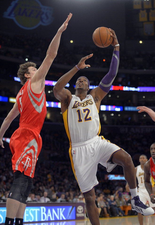 Los Angeles Lakers center Dwight Howard, right, puts up a shot as Houston Rockets center Omer Asik, of Turkey, defends during the first half of their NBA basketball game, Sunday, Nov. 18, 2012, in Los Angeles. (AP Photo/Mark J. Terrill)