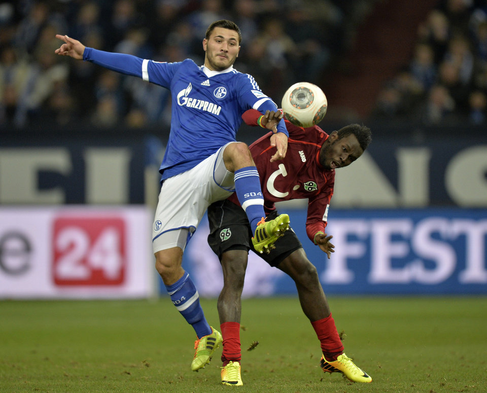 Photo - Schalke's Sead Kolasinac, left, and Hannover's Mame Diouf challenge for the ball during the German Bundesliga soccer match between FC Schalke  and SV Hannover in Gelsenkirchen,  Germany, Sunday, Feb. 9, 2014. (AP Photo/Martin Meissner)