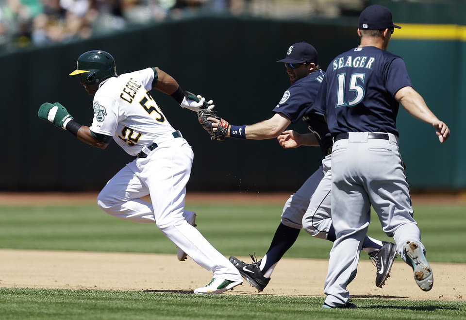 Photo - Oakland Athletics' Yoenis Cespedes, left, is tagged out in a rundown between second and third base by Seattle Mariners shortstop Brad Miller in the second inning of a baseball game Sunday, April 6, 2014, in Oakland, Calif. Assisting on the play is Kyle Seager (15). (AP Photo/Ben Margot)