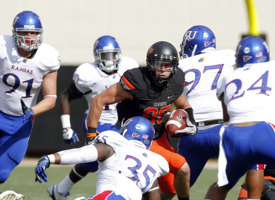 Photo - Oklahoma State's Josh Cooper (25) looks to get past a host of Kansas defenders during the first half of the college football game between the Oklahoma State University Cowboys (OSU) and the University of Kansas Jayhawks (KU) at Boone Pickens Stadium in Stillwater, Okla., Saturday, Oct. 8, 2011. Photo by Sarah Phipps, The Oklahoman