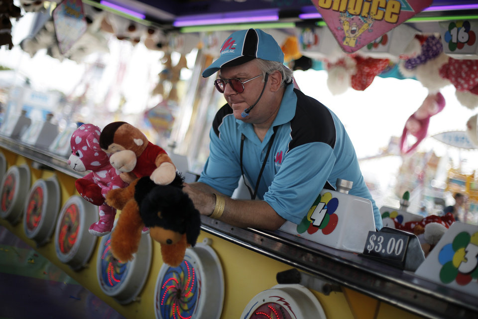 Andrew Cashman hands toys to a winner at his booth at the Oklahoma State Fair in Oklahoma City, Friday, Sept. 21, 2012.  Photo by Garett Fisbeck, The Oklahoman