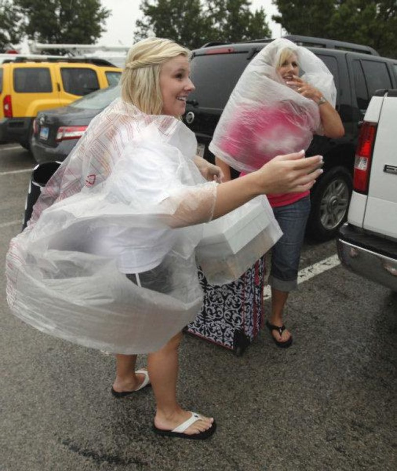 Photo - Lindsey and her mother Lisa Scott, Oklahoma City, cover up as Lindsey moves into a dormitory at the University of Oklahoma as heavy rain falls on Thursday, August 11, 2011, in Norman, Okla.  Photo by Steve Sisney, The Oklahoman ORG XMIT: KOD