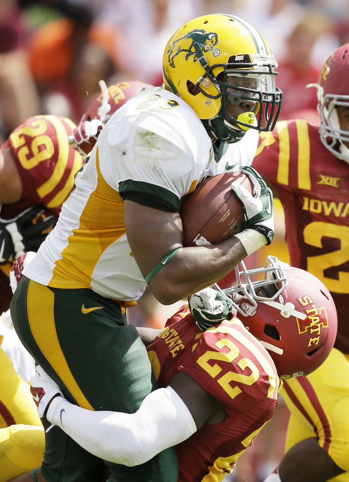 Photo - North Dakota State running back John Crockett runs over Iowa State defensive back T.J. Mutcherson during the second half of an NCAA college football game, Saturday, Aug. 30, 2014, in Ames, Iowa. North Dakota State won 34-14. (AP Photo/Charlie Neibergall)