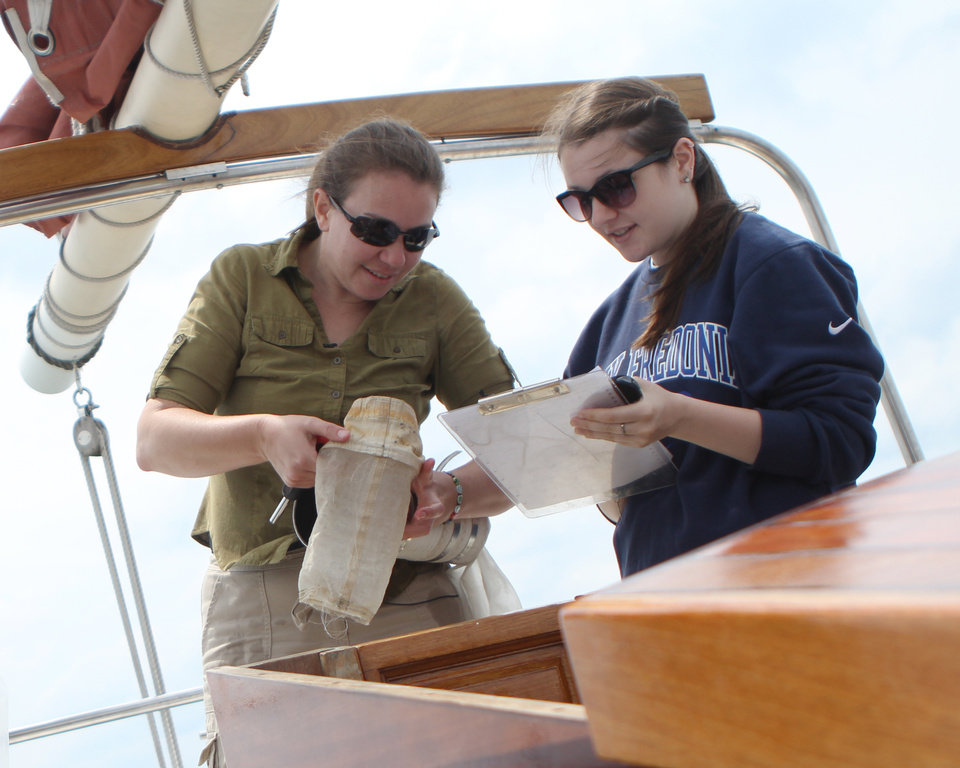 """Photo - In this June 2014 photo provided by State University of New York at Fredonia Sherri Mason, left, a New York environmental scientist who led a research team studying microplastics in the Great Lakes, examines a trawling device used to collect plastic """"microbeads"""" from the water's surface with SUNY-Fredonia student Rachel Ricotta in Lake Erie's Buffalo Harbor. Illinois environmentalists expecting a battle with business over a call for a ban on the tiny bits of plastic used in personal care products, found the industry quickly collaborated. With similar bans pending in at least three other large states, the extinction of microbeads, now showing up inside fish that are caught for human consumption, is happening in an unusually short amount of time. (AP Photo/SUNY-Fredonia)"""