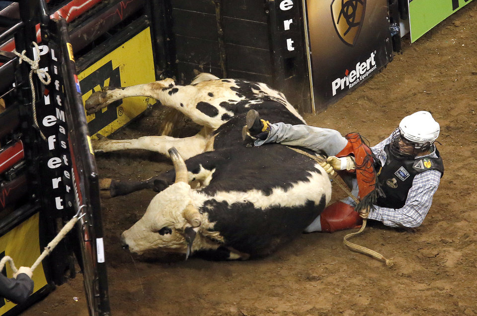 Breakdown falls to the ground on top of Lachlan Richardson during the WinStar World Casino Invitational PBR bull riding event at Chesapeake Energy Arena in Oklahoma City, Sunday, Jan. 27, 2013.Photo by Sarah Phipps, The Oklahoman