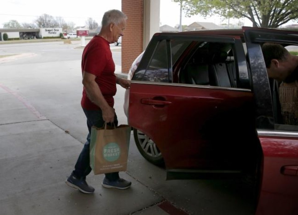 Photo -  Joe Potter loads a sack of groceries into a car during the church's