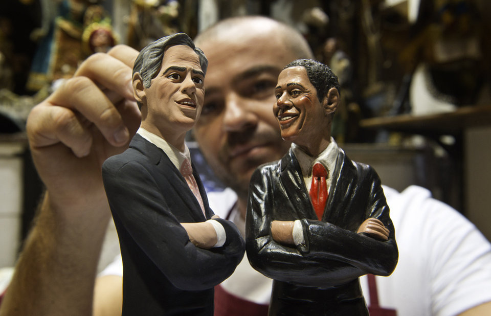 Photo -   Italian Nativity scenes designer Genny Di Virgilio puts the final touches on two statuettes depicting President Barack Obama, right, and Republican rival Mitt Romney in his shop in Naples, Italy, Monday, Oct. 22, 2012, hours ahead of their third and final presidential debate in Boca Raton, Florida. (AP Photo/Salvatore Laporta)