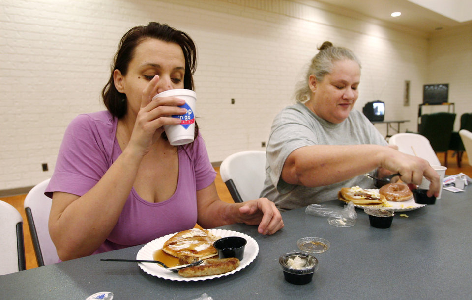 Photo - Melissa Hall, left, and her mother, Cristy  Bryant, eat breakfast at a Red Cross shelter in the Nick Harroz Community Center in Midwest Center Friday, April 10, 2009.  The women and their children spent Thursday night at the shelter. They said they were able to get a few hours sleep. Photo by Jim Beckel, The Oklahoman