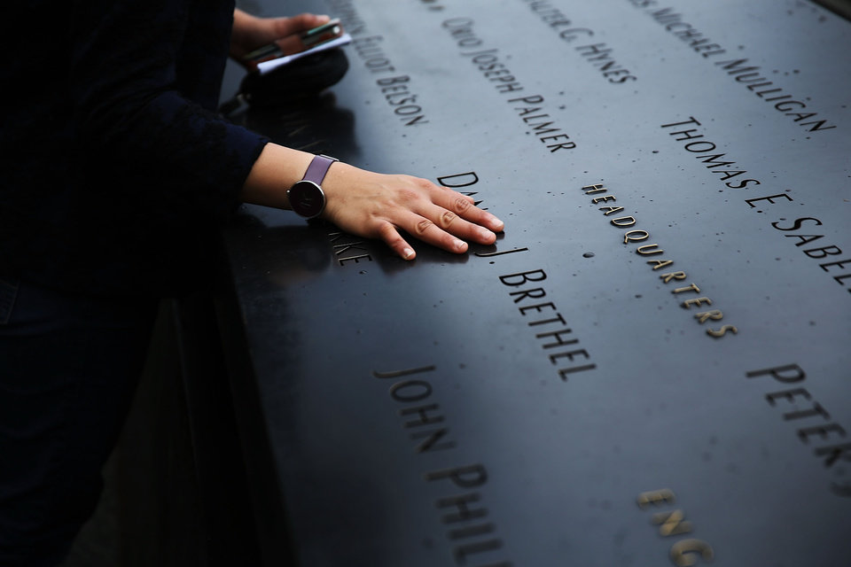 Photo - A woman places a hand on the names engraved along the South reflecting pool at the Ground Zero memorial site during the dedication ceremony of the National September 11 Memorial Museum in New York on Thursday, May 15, 2014.  (AP Photo/Spencer Platt, Pool)