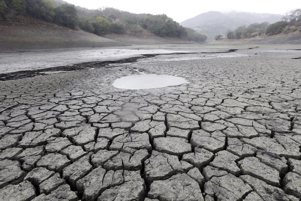 Photo - FILE - This Feb. 7, 2014, file photo shows the cracked-dry bed of the Almaden Reservoir in San Jose, Calif.   Global warming is rapidly turning America the beautiful into America the stormy, sneezy and dangerous, according to a new federal scientific report. And those shining seas? Rising and costly, the report says.  (AP Photo/Marcio Jose Sanchez, File)