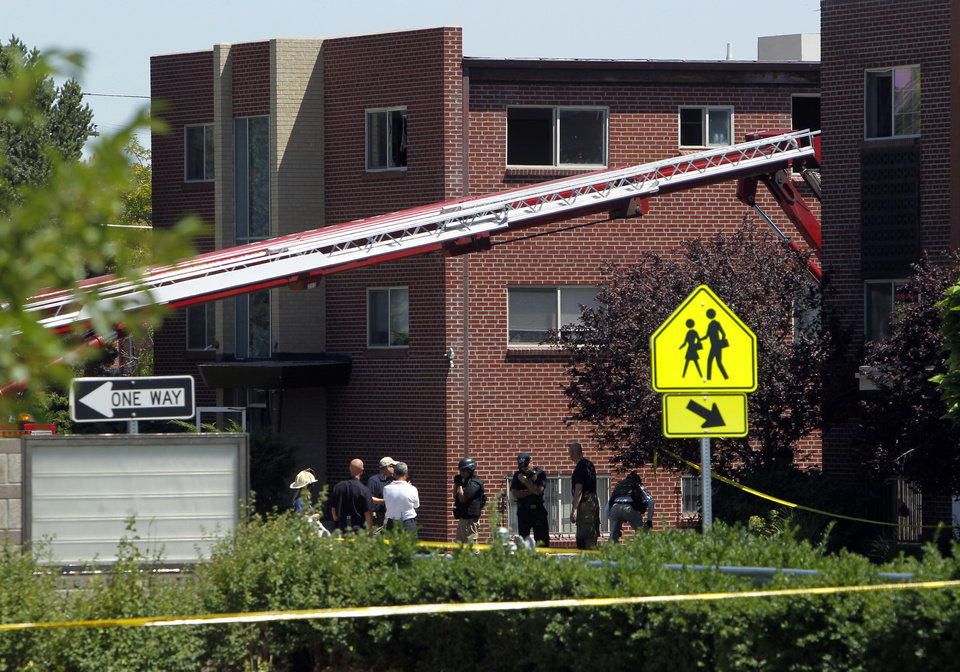 Photo -   Firefighters and police gather after an explosion could be heard in front the apartment of shooting suspect James Holmes in Aurora, Colo., Saturday, July 21, 2012. Federal authorities detonated one small explosive and disarmed another inside Holmes' apartment, but several other explosive devices remained, said Aurora police Sgt. Cassidee Carlson. Twelve people were killed and dozens were injured in a shooting attack early Friday at a packed movie theater during a showing of the Batman movie,