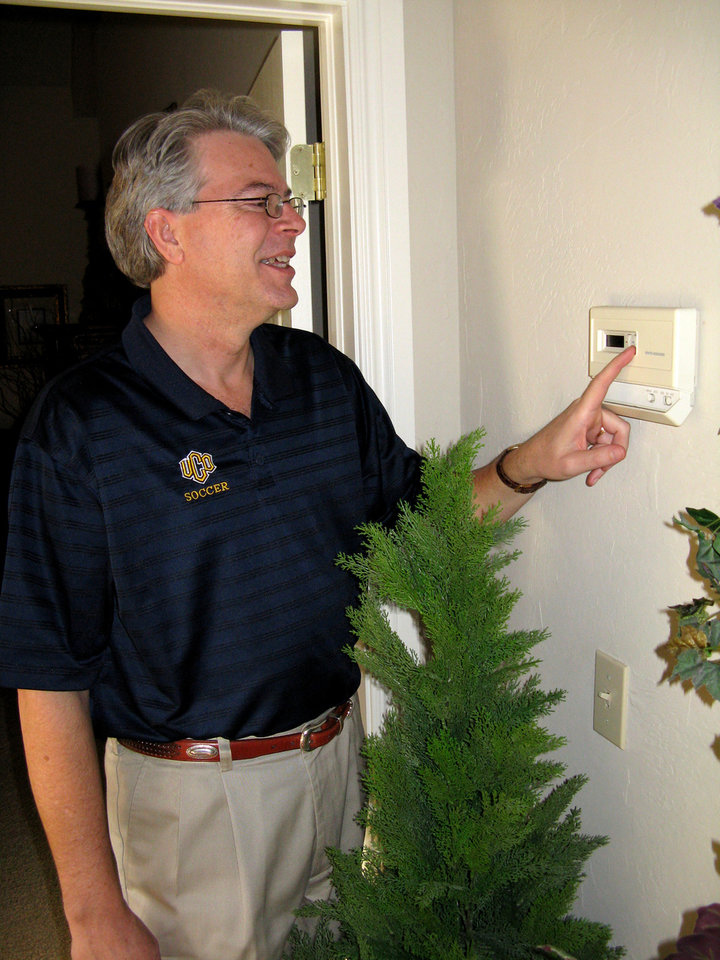 Photo - Edmond homeowner and University of Central Oklahoma executive vice president Steve Kreidler changes the setting on his home's thermostat. Kreidler has signed up to buy wind power provided by Edmond Electric. BY MICAH GAMINO, THE OKLAHOMAN ORG XMIT: 0803121617257465