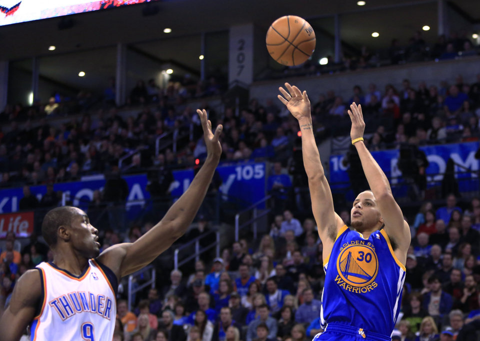 Photo - Golden State Warriors guard Stephen Curry (30) shoots as Oklahoma City Thunder forward Serge Ibaka defends during the second quarter of an NBA basketball game Friday, Jan. 17, 2014, in Oklahoma City. (AP Photo/Alonzo Adams)