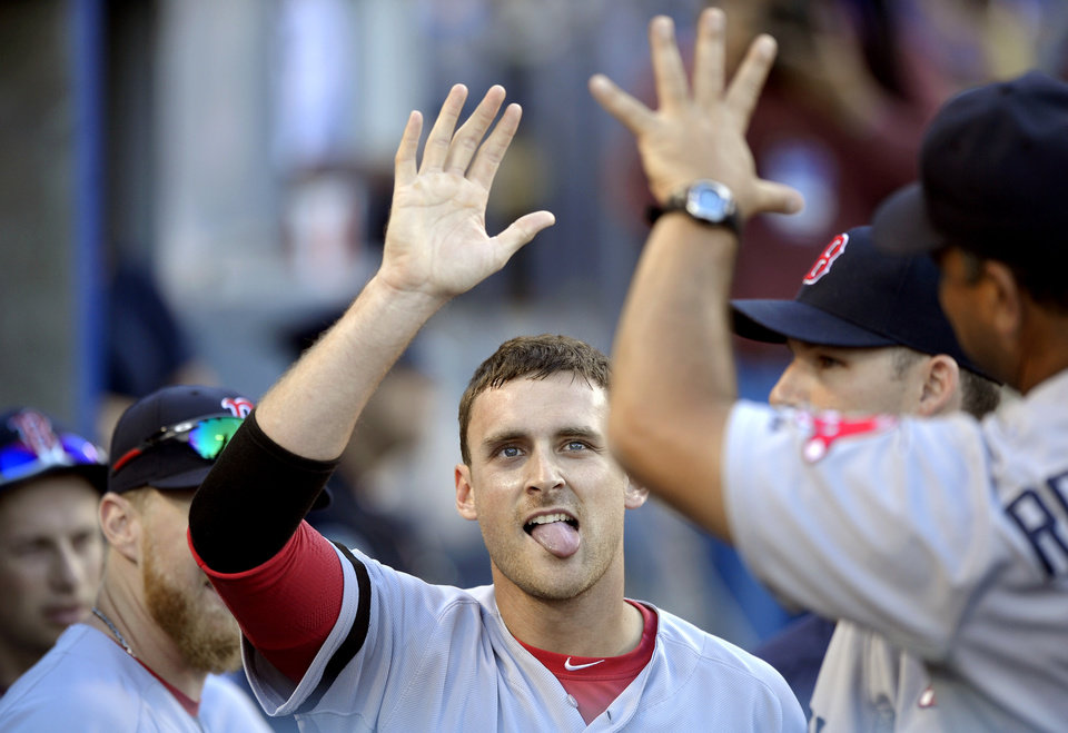 Photo - Boston Red Sox's Will Middlebrooks is congratulated by teammates after scoring on double by Xander Bogaerts during the fourth inning of their baseball game against the Los Angeles Dodgers, Sunday, Aug. 25, 2013, in Los Angeles.  (AP Photo/Mark J. Terrill)