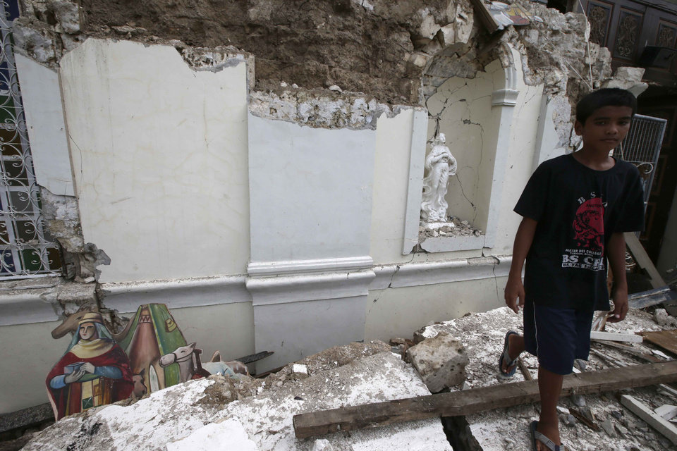 Photo - A boy walks away from the rubble of San Isidro de Labrador church which was caused by a 7.2-magnitude earthquake  at Tubigon  township, Bohol province in central Philippines Wednesday Oct. 16, 2013. A 7.2-magnitude quake hit Bohol and Cebu provinces Tuesday damaging churches, buildings and homes and causing multiple deaths across the central region and sending terrified residents into deadly stampedes. (AP Photo/Bullit Marquez)