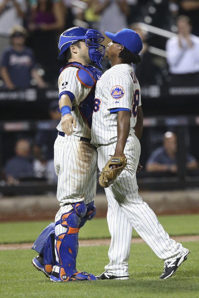 Photo - New York Mets relief pitcher Jenrry Mejia, right, and catcher Travis d'Arnaud celebrate after a baseball game against the Atlanta Braves, Tuesday, Aug. 26, 2014, in New York. The Mets won 3-2. (AP Photo/John Minchillo)