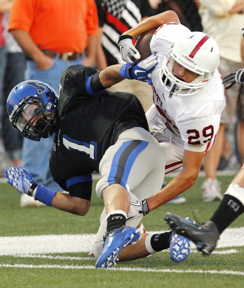 Photo - Tuttle's Jake Welch (29) is stopped by Newcastle's Cade Nichols (1) as the Racers play the Tuttle Tigers in high school football on Friday, September 9, 2011, in Newcastle, Okla.   Photo by Steve Sisney, The Oklahoman