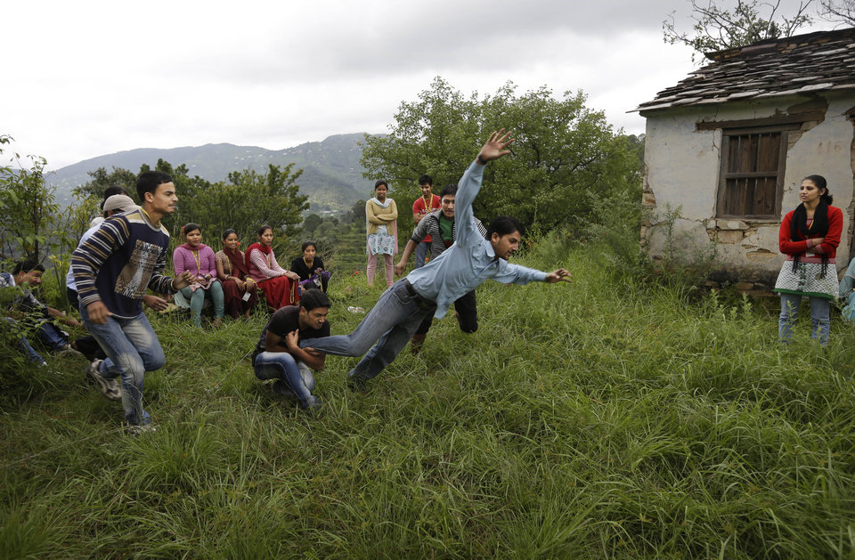 Photo -   In this Aug. 25, 2012 photo, employees play a game of kabaddi as a team building exercise at the beginning of their working day near a B2R center in Simayal, India. (AP Photo/Saurabh Das)