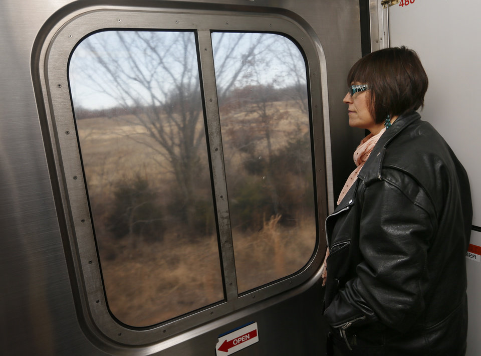 Photo - Marcy Janitz of Tulsa, Okla., looks out of a window on a demonstration ride of the Eastern Flyer passenger train from Sapulpa to the Oklahoma City metro area, Sunday, Feb. 23, 2014. Photo by Nate Billings, The Oklahoman
