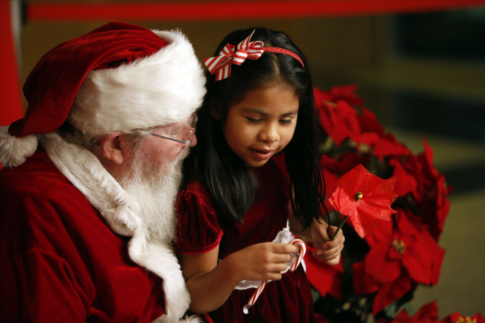 """Photo - Alisa Lindsey, 6, visits with Santa Claus during the """"Holiday Happening"""" on Thursday at the Sam Noble Oklahoma Museum of Natural History. PHOTOS BY STEVE SISNEY, THE OKLAHOMAN"""