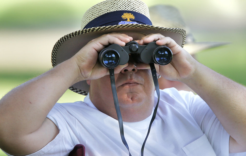 Photo - Charles Dunagan looks through his binoculars to get a closer look at the action during practice rounds for the U.S. Senior Open golf tournament at Oak Tree National in Edmond, Okla. on Tuesday, July 8, 2014. Photo by Chris Landsberger, The Oklahoman