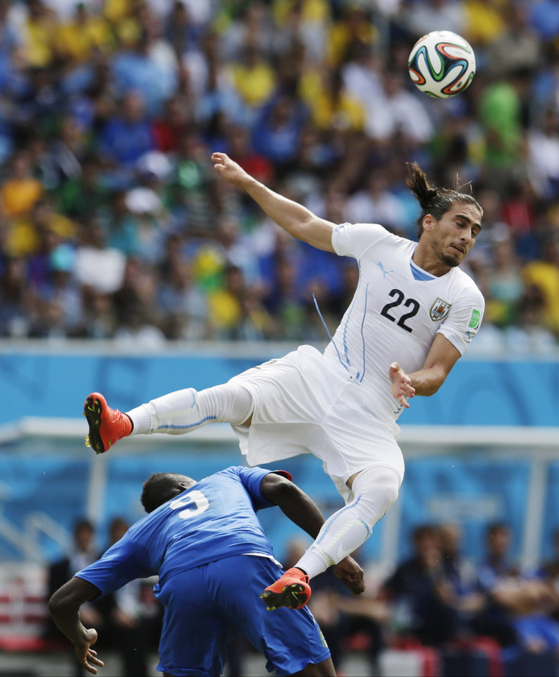 Photo - Italy's Mario Balotelli gets underneath Uruguay's Martin Caceres as he tries to head the ball during the group D World Cup soccer match between Italy and Uruguay at the Arena das Dunas in Natal, Brazil, Tuesday, June 24, 2014. (AP Photo/Petr David Josek)