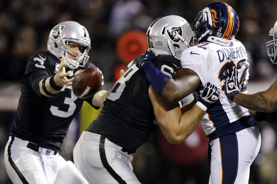 Photo - Oakland Raiders tackle Jared Veldheer blocks Denver Broncos defensive tackle Mitch Unrein, right, as Raiders quarterback Carson Palmer (3) loses control of the ball during the third quarter of an NFL football game in Oakland, Calif., Thursday, Dec. 6, 2012. (AP Photo/Marcio Jose Sanchez)