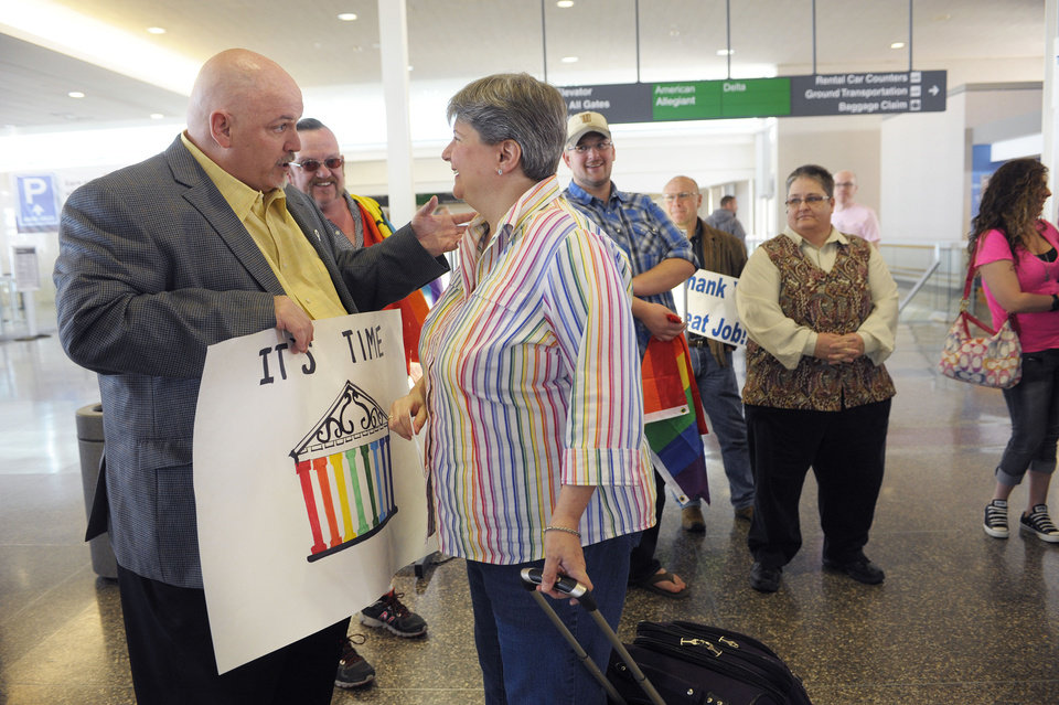 Photo - From left, Toby Jenkins speaks with Sharon Baldwin before Baldwin boarded a plane to Denver, Wednesday April 16, 2014. Oklahomans for Equality gathered at Tulsa International Airport with their signs for a send off celebration in support for the plaintiffs, including Sharon Baldwon, in the Oklahoma Marriage Equality lawsuit as they head to the 10th Circuit Court of Appeals in Denver. (AP Photo/Brandi Simons)