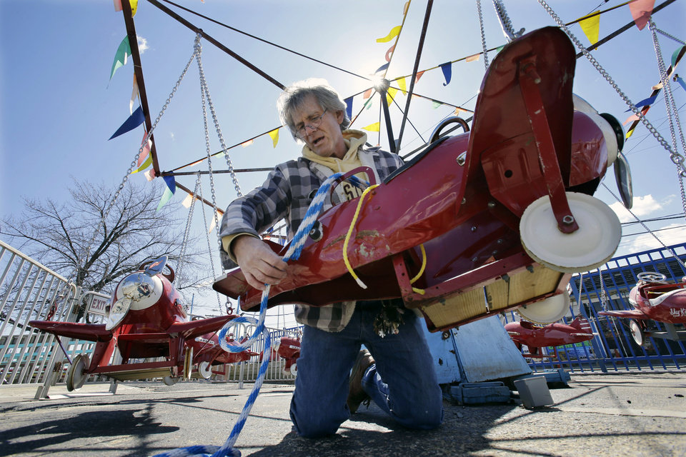Hank Gehlhaus prepares the 1930's Kiddie Airplane Ride for opening day at The Keansburg Amusement Park, Saturday, March 23, 2013, in Keansburg, N.J. Founded in 1904, by Gehlhaus' grandfather, the Keansburg Amusement Park, which Superstorm Sandy left under up to six feet of water, opens Saturday even though not all rides will be ready to operate and its popular Wildcat roller coaster is gone. (AP Photo/Mel Evans)