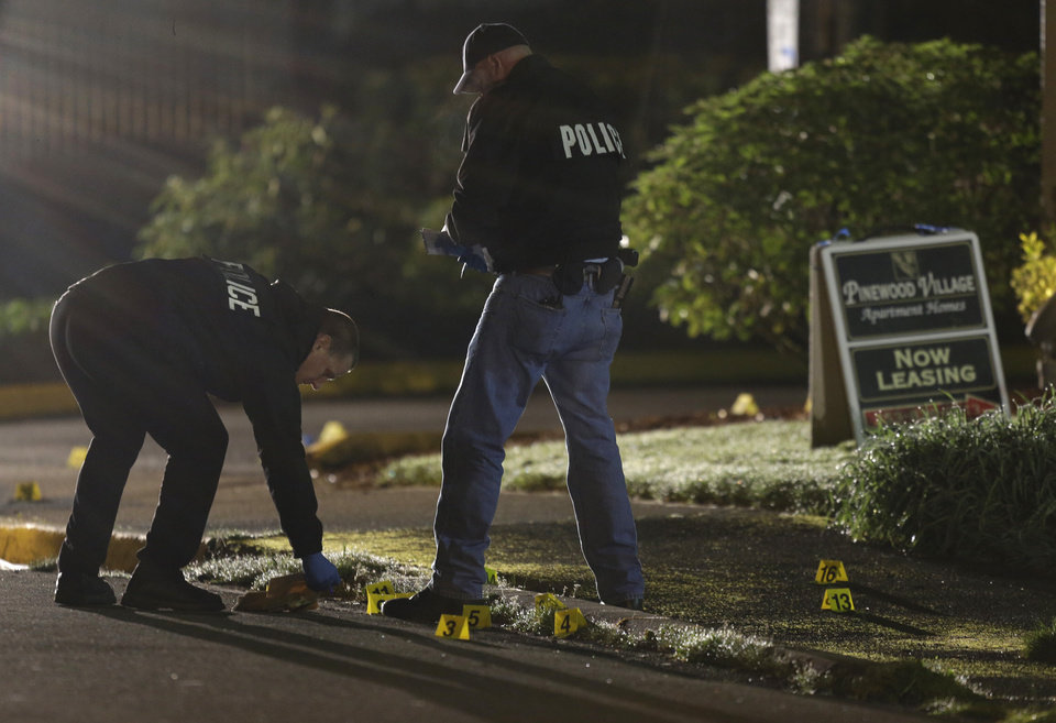 Photo - Police officers gather evidence at the scene of an overnight shooting that left five people dead, including a suspect who was shot by arriving officers, police said early Monday, April 22, 2013, at the Pinewood Village apartment complex in Federal Way, Wash. (AP Photo/Ted S. Warren)