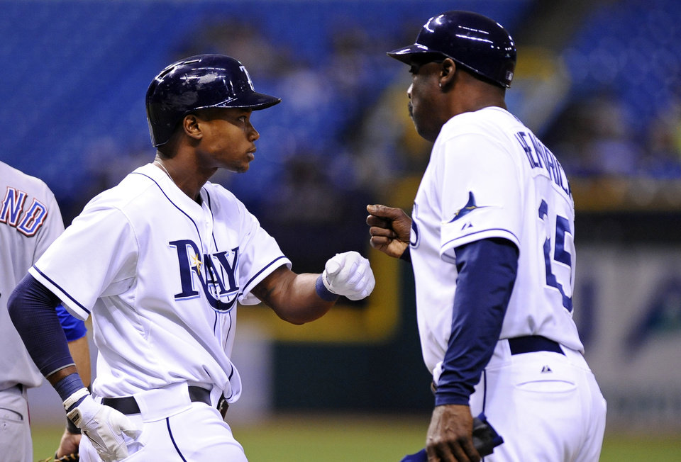 Tampa Bay Rays' Tim Beckham, left, celebrates with Rays first base coach George Hendrick after hitting a single during the eighth inning of a baseball game against the Texas Rangers, Thursday, Sept. 19, 2013, in St. Petersburg, Fla. (AP Photo/Brian Blanco)