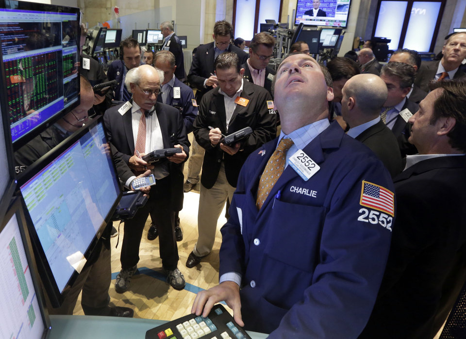 Photo - Specialist Charles Boedinghaus, foreground, check a board at his post on the floor of the New York Stock Exchange Friday, Aug. 16, 2013. Stocks bounced back Friday from consecutive days of significant declines, with more evidence of a rebounding U.S. housing market. (AP Photo/Richard Drew)