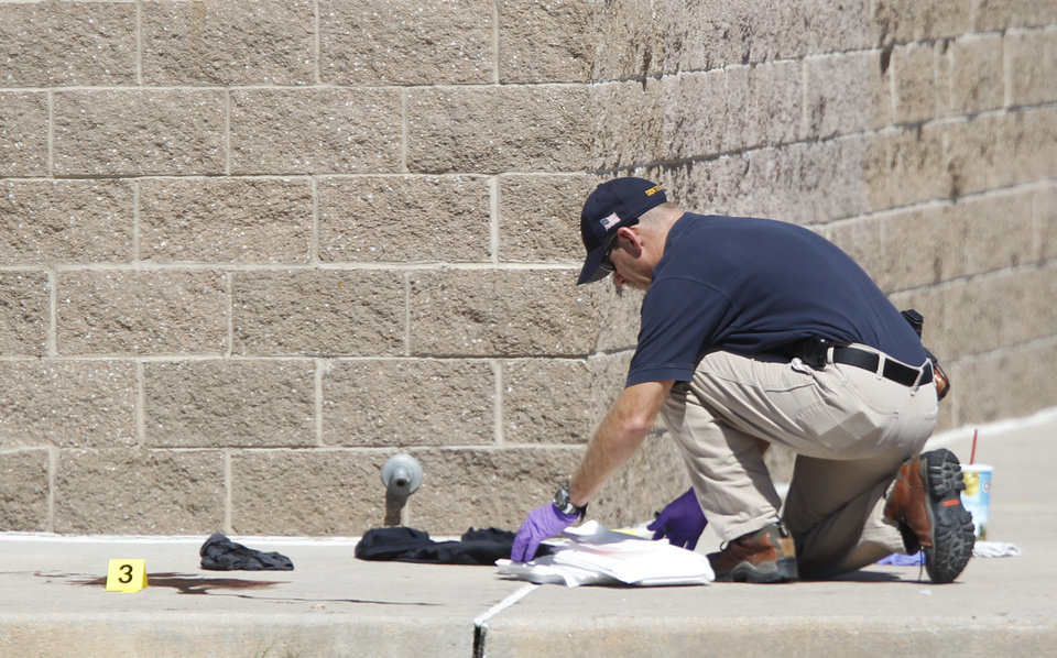 Photo - An investigator inspects evidence outside the Century 16 movie theater east of the Aurora Mall in Aurora, Colo. on Friday, July 20, 2012. A gunman in a gas mask barged into the crowded Denver-area theater during a midnight showing of the Batman movie on Friday, hurled a gas canister and then opened fire in one of the deadliest mass shootings in recent U.S. history. (AP Photo/David Zalubowski) ORG XMIT: CODZ116