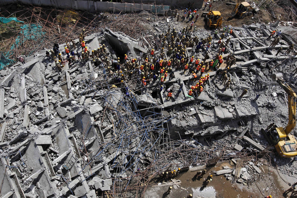 Photo - Rescuers, search for workers believed buried in the rubble of a building that collapsed late Saturday during monsoon rains on the outskirts of Chennai, India, Sunday, June 29, 2014. Police said dozens of workers have been pulled out so far and the search is continuing. (AP Photo/Arun Sankar K)