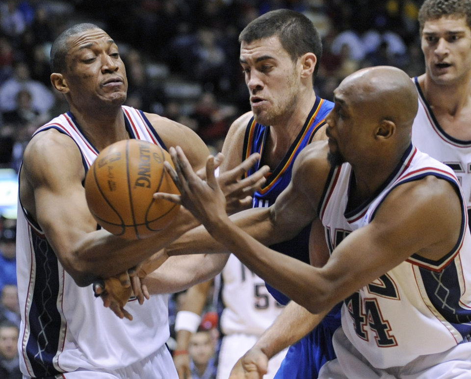 New Jersey Nets' Tony Battie, left, and Trenton Hassell, right, battle for control of the ball with Oklahoma City Thunder forward Nick Collison during the fourth quarter of an NBA basketball game Monday, Dec. 28, 2009, in East Rutherford, N.J. The Thunder beat the Nets 105-89. (AP Photo/Bill Kostroun) ORG XMIT: ERA108