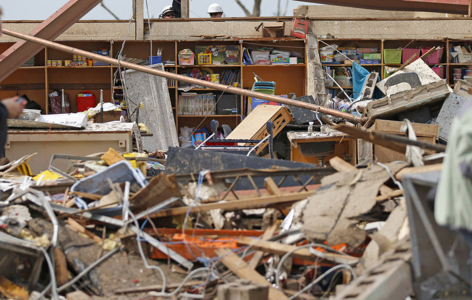 Workers look over a wall at the Plaza Towers Elementary School in Moore, Okla., on Tuesday, May 21, 2013. A tornado hit the area on Monday, May 20, 2013. Photo by Bryan Terry, The Oklahoman