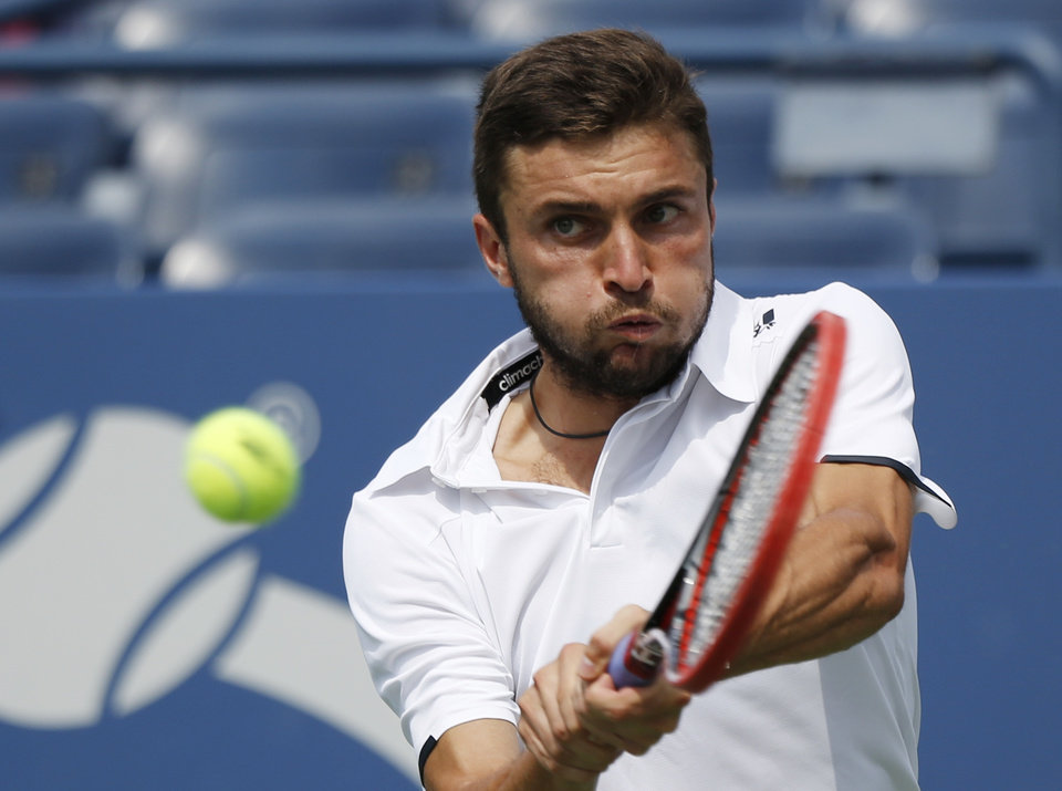 Photo - Gilles Simon, of France, returns a shot against David Ferrer, of Spain, of the 2014 U.S. Open tennis tournament, Sunday, Aug. 31, 2014, in New York. (AP Photo/Seth Wenig)