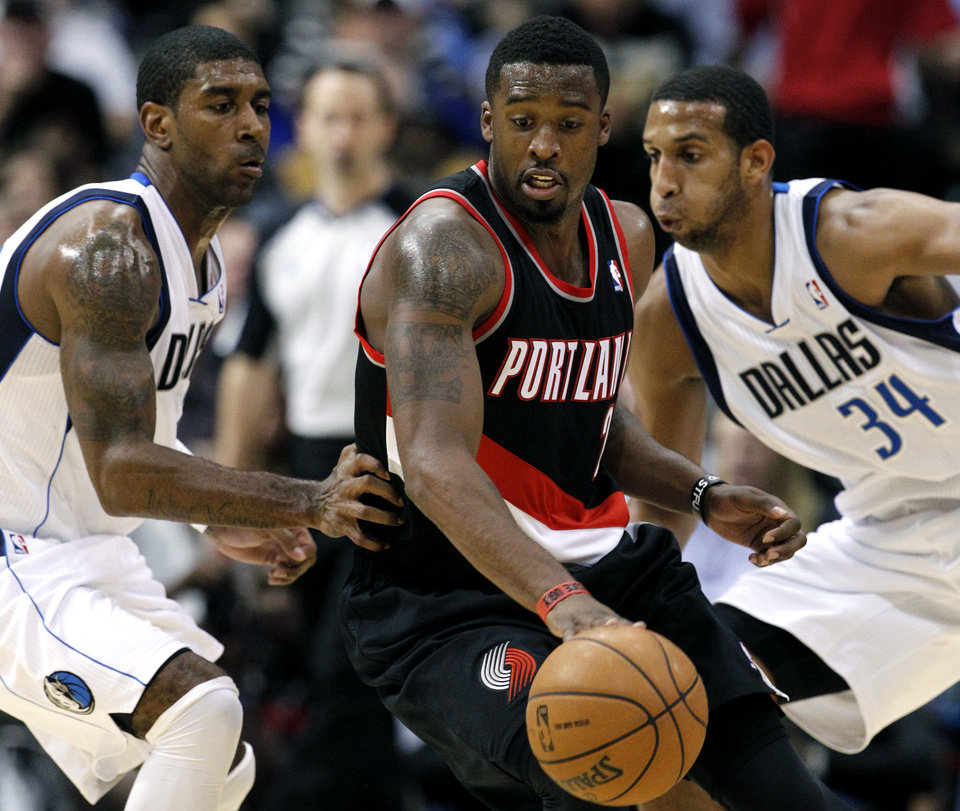 Portland Trail Blazers' Wesley Matthews (2) looks for an opening against Dallas Mavericks' O.J. Mayo, left, and Brandan Wright (34) during the second half of an NBA basketball game Monday, Nov. 5, 2012, in Dallas. Matthews had 20 points in the 114-91 loss to the Mavericks. (AP Photo/Tony Gutierrez)
