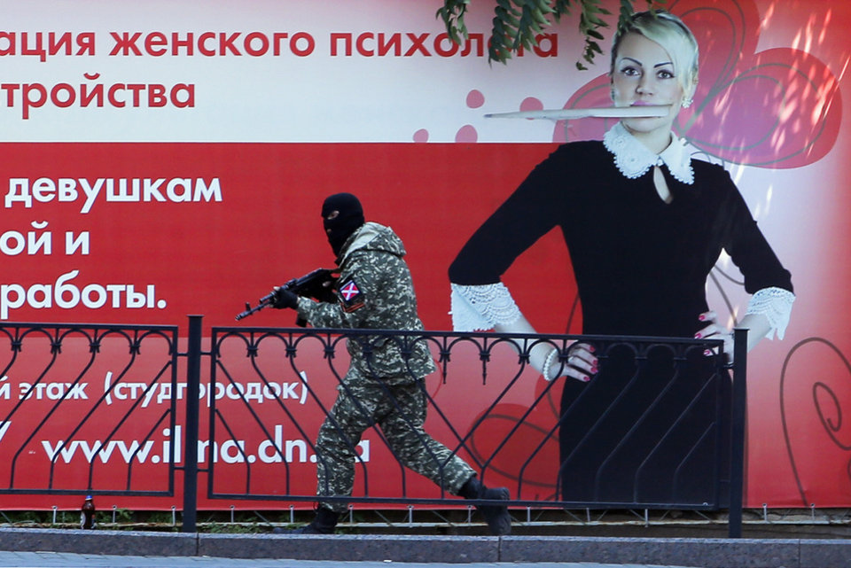 Photo - A pro-Russian fighter runs past a huge poster during fighting near a regional police department in downtown Donetsk, eastern Ukraine, Tuesday, July 1, 2014. Ukraine renewed its attacks against armed pro-Russian separatists Tuesday after the president called off a unilateral cease-fire, carrying out air and artillery strikes against rebel positions in eastern Ukraine. (AP Photo/Dmitry Lovetsky)