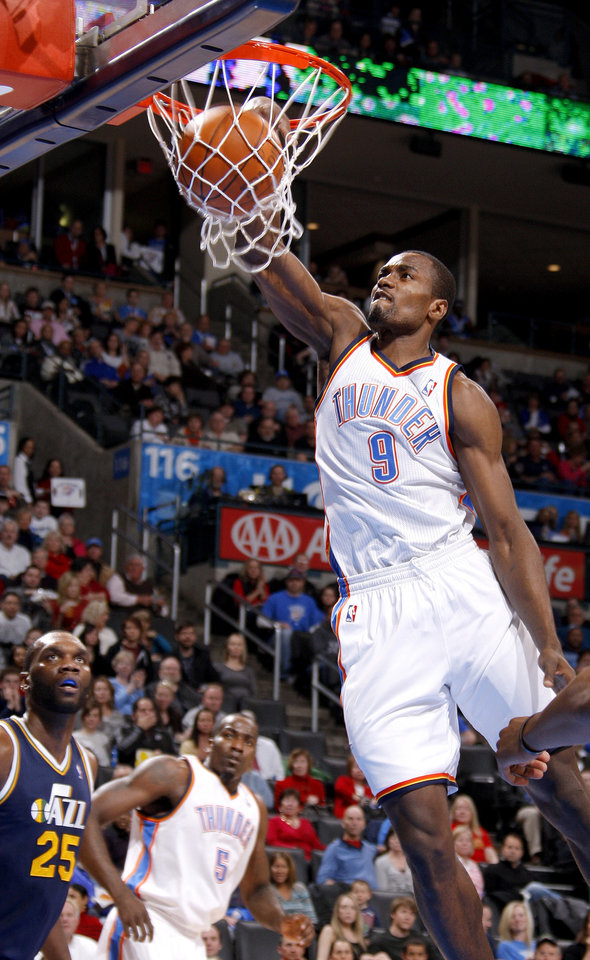 Photo - Oklahoma City's Serge Ibaka (9) dunsk the ball as Utah's Al Jefferson (25) watches during an NBA game between the Oklahoma City Thunder and the Utah Jazz at Chesapeake Energy Arena in Oklahoma CIty, Tuesday, Feb. 14, 2012. Photo by Bryan Terry, The Oklahoman