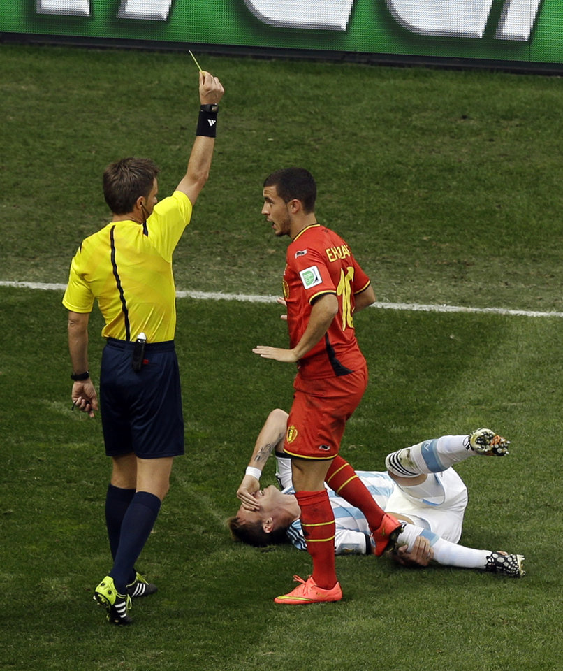 Photo - Referee Nicola Rizzoli from Italy issues a yellow card to Belgium's Eden Hazard for a foul against Argentina's Lucas Biglia, bottom during the World Cup quarterfinal soccer match between Argentina and Belgium at the Estadio Nacional in Brasilia, Brazil, Saturday, July 5, 2014. (AP Photo/Thanassis Stavrakis)