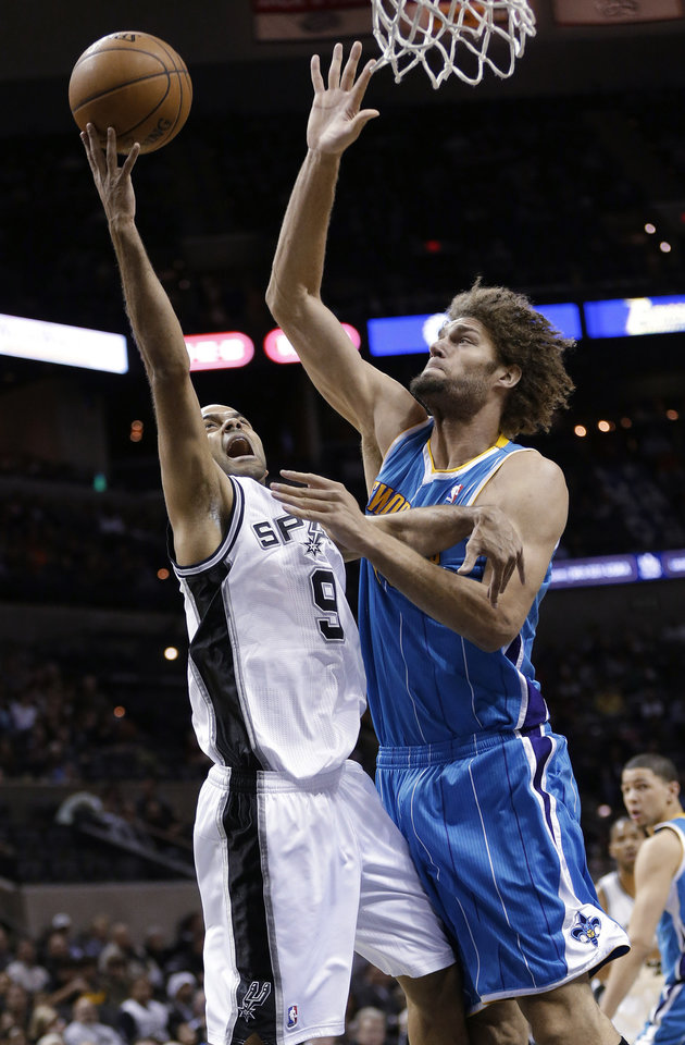 San Antonio Spurs' Tony Parker (9) shoots as New Orleans Hornets' Robin Lopez defends during the first quarter of an NBA basketball game, Friday, Dec. 21, 2012, in San Antonio. (AP Photo/Eric Gay)