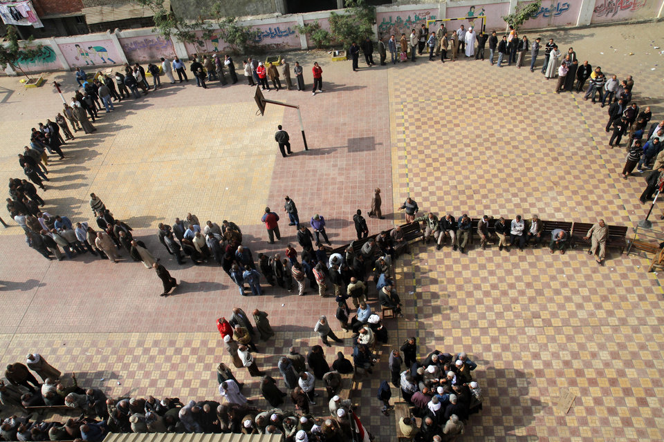 Egyptians wait in line to cast their votes during a referendum on a disputed constitution drafted by Islamist supporters of President Morsi in Cairo, Egypt, Saturday, Dec. 15, 2012. (AP Photo/Ahmed Gomaa)